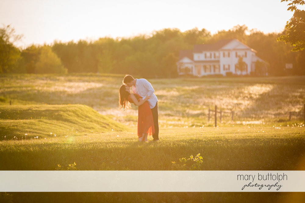 Couple kiss in the meadow in front of the hotel at Skaneateles Engagement