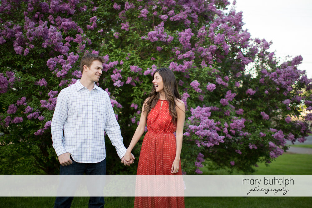Couple holds hands in front of a flowering tree at Skaneateles Engagement