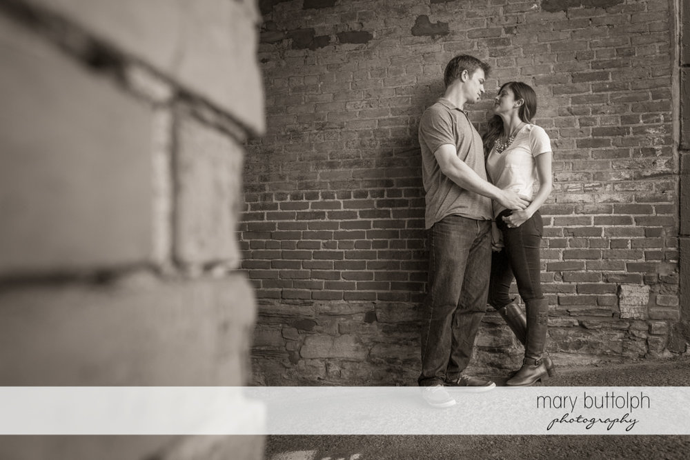 Couple pose in front of a brick wall at Skaneateles Engagement