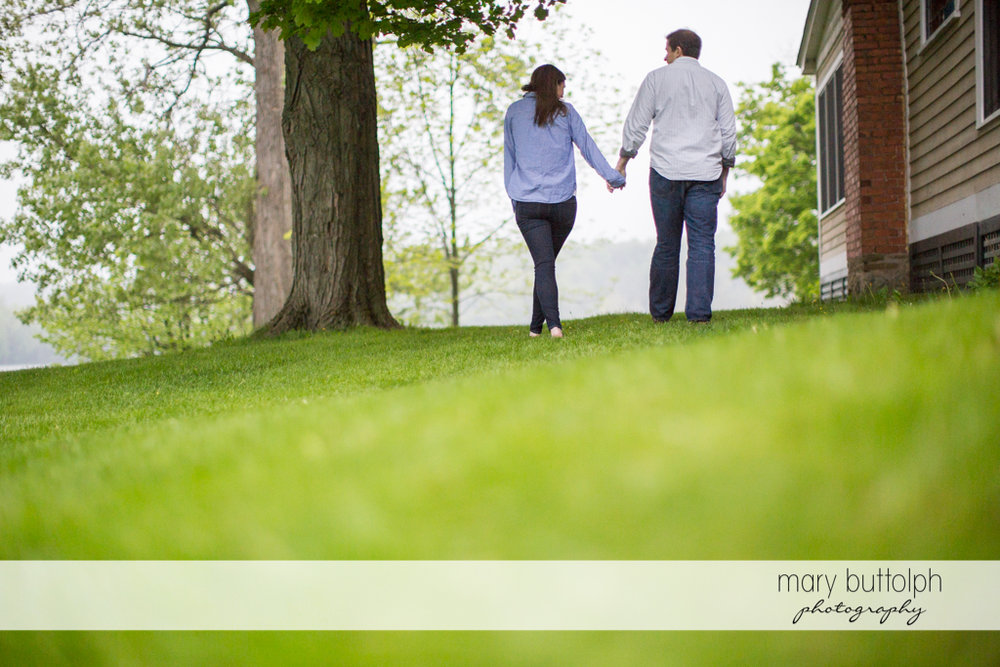 Couple hold hands while walking in the garden at the Hamilton Inn Engagement
