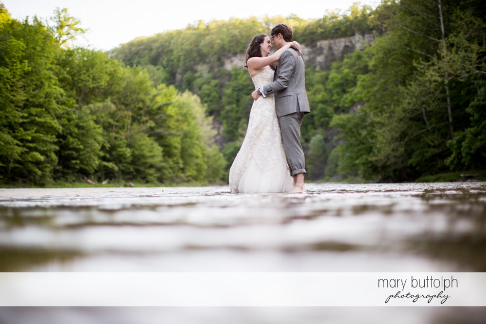 Couple embrace in the middle of the lake at Taughannock Falls Wedding