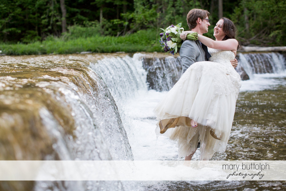Groom carries the bride across the lake at Taughannock Falls Wedding