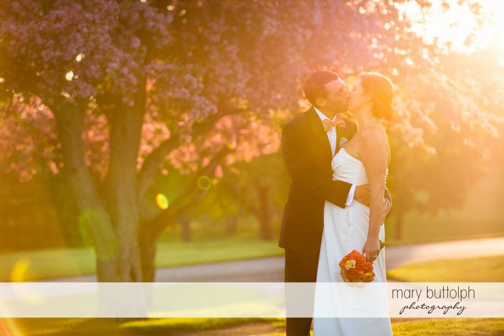 Couple kiss on the lawn at Skaneateles Country Club Wedding