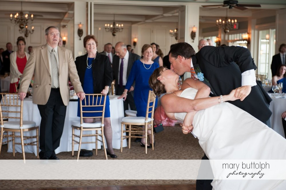 Couple kiss as guests look on at Skaneateles Country Club Wedding