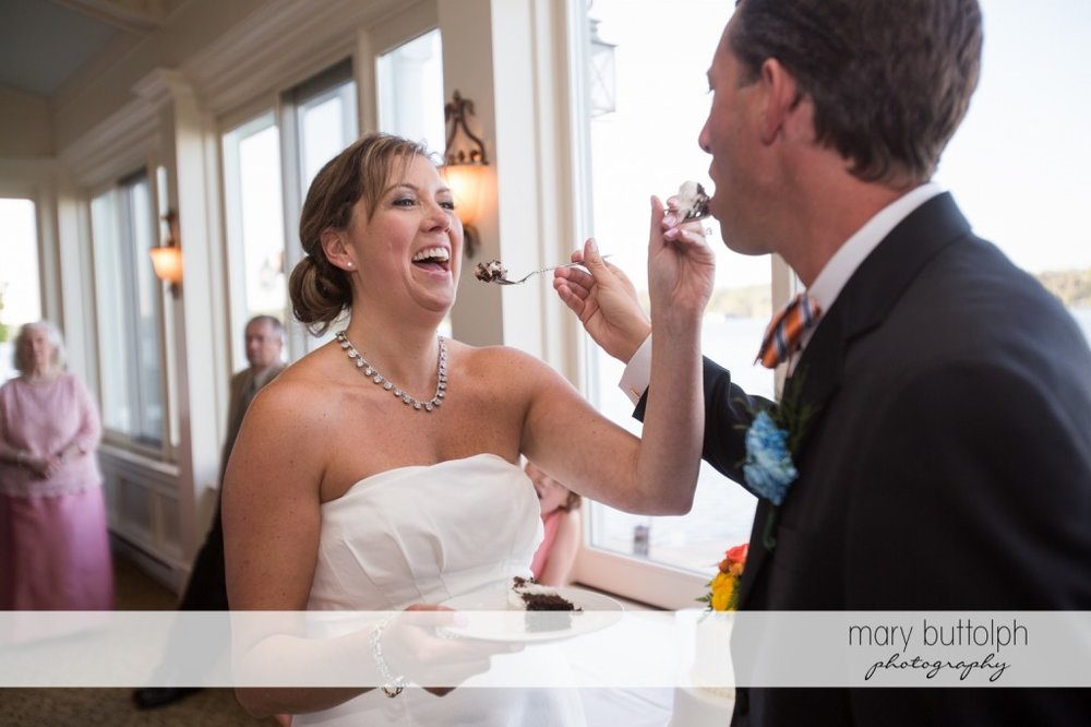 Couple feed each other with the wedding cake at Skaneateles Country Club Wedding