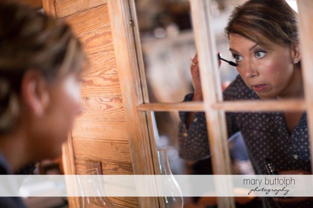 Bride applies mascara to her eyelashes at Skaneateles Country Club Wedding