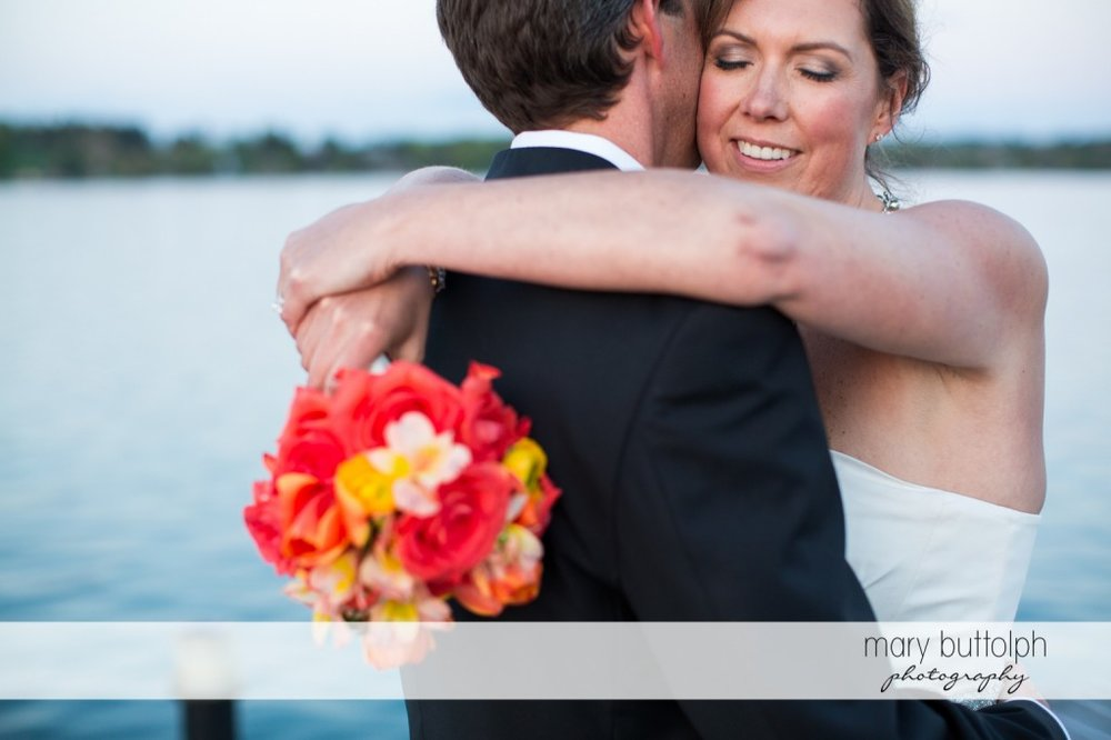 Couple embrace by the lake at Skaneateles Country Club Wedding
