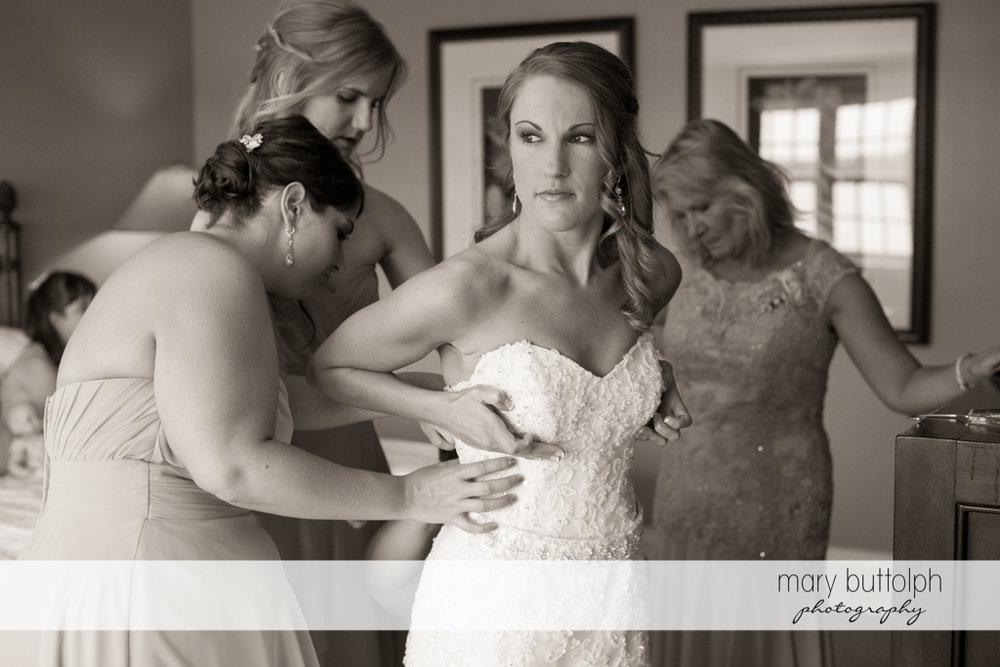 Bridesmaids fix the bride's wedding dress at the Inns of Aurora Wedding