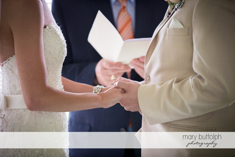 Couple holds hands in front of the wedding officiant at the Inns of Aurora Wedding