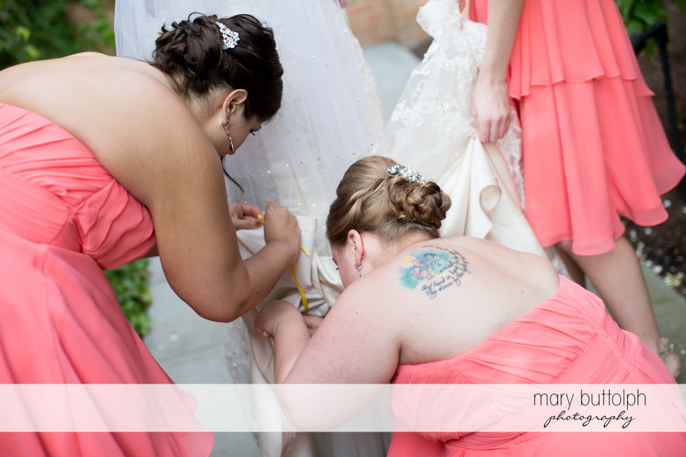 Bridesmaids busy fixing the bride's wedding dress at the Inns of Aurora Wedding