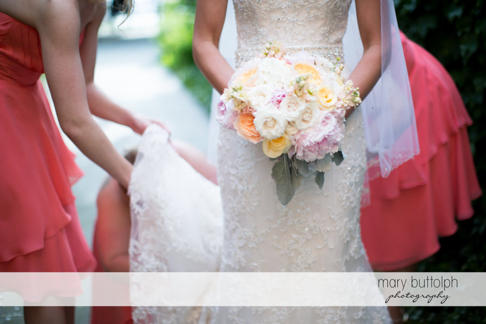 Bridesmaids hold the bride's wedding dress at the Inns of Aurora Wedding