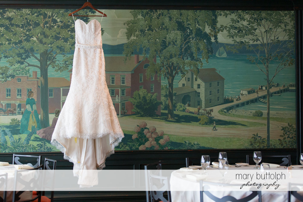Bride's wedding dress hangs from a huge painting at the Inns of Aurora Wedding