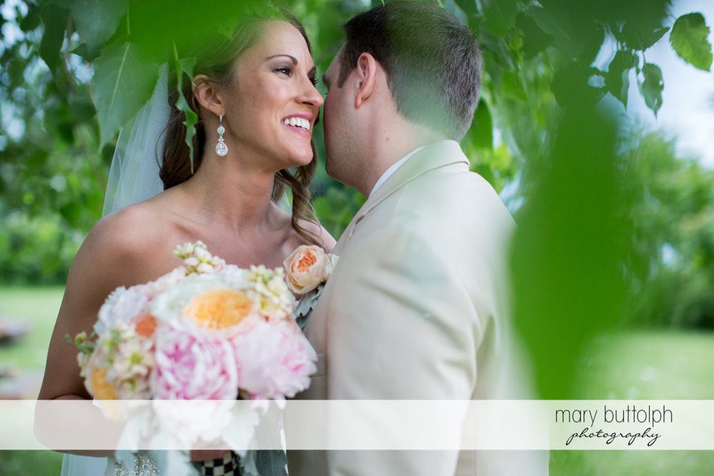 Groom whispers to the bride in the garden at the Inns of Aurora Wedding