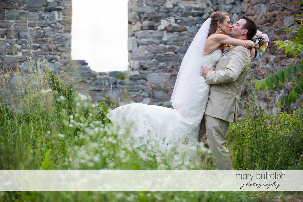 Couple kiss by the ruins at the Inns of Aurora Wedding