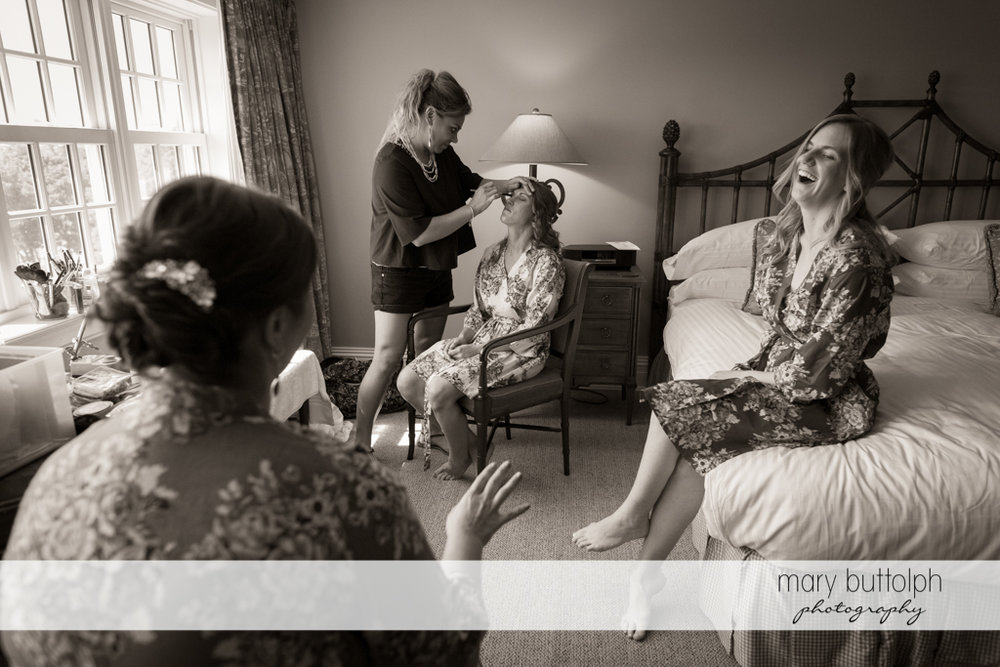Bride gets a makeover while the bridesmaids find something funny at the Inns of Aurora Wedding