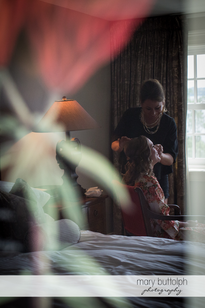 Bride gets a touch up near the window at the Inns of Aurora Wedding