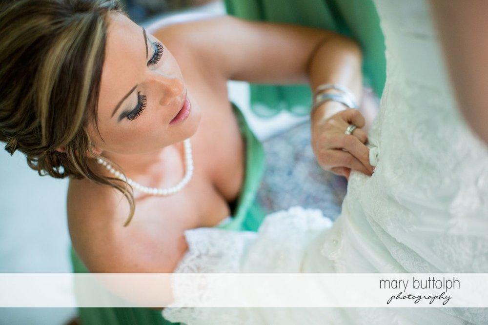 Bridesmaid fixes the bride's wedding dress at Emerson Park Pavilion Wedding