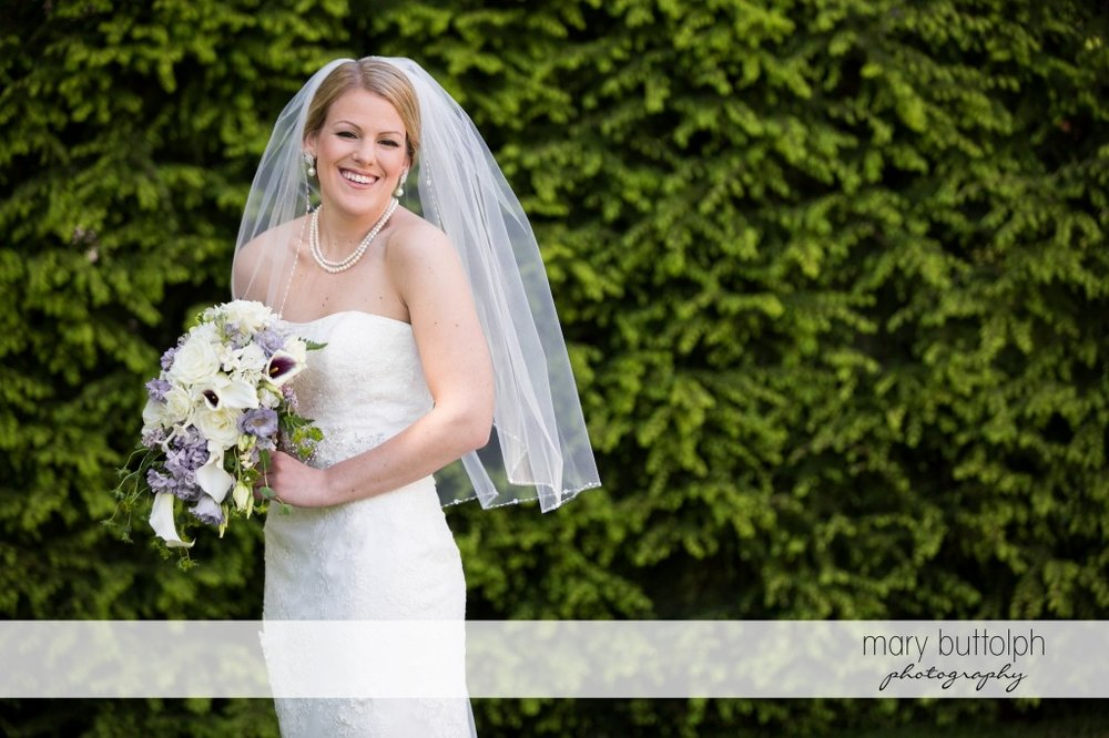 Bride with bouquet poses in the garden at Emerson Park Pavilion Wedding