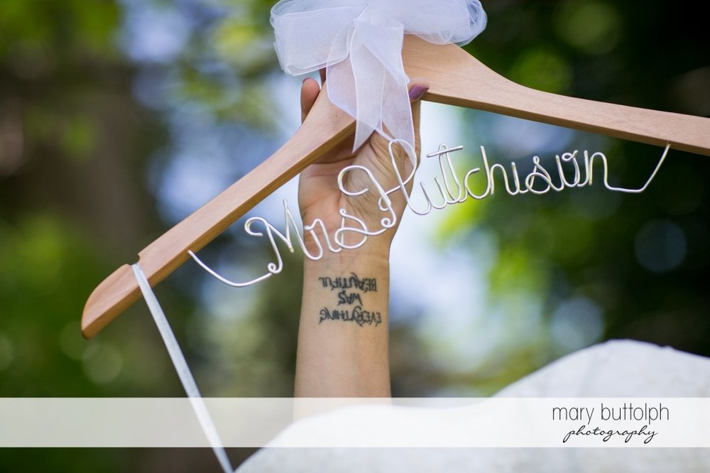 Tattooed bride shows her personalized hanger at Emerson Park Pavilion Wedding