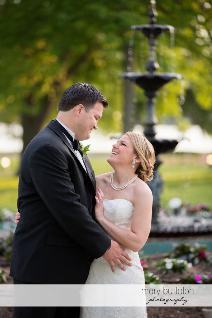 Couple pose in front of the fountain at Emerson Park Pavilion Wedding