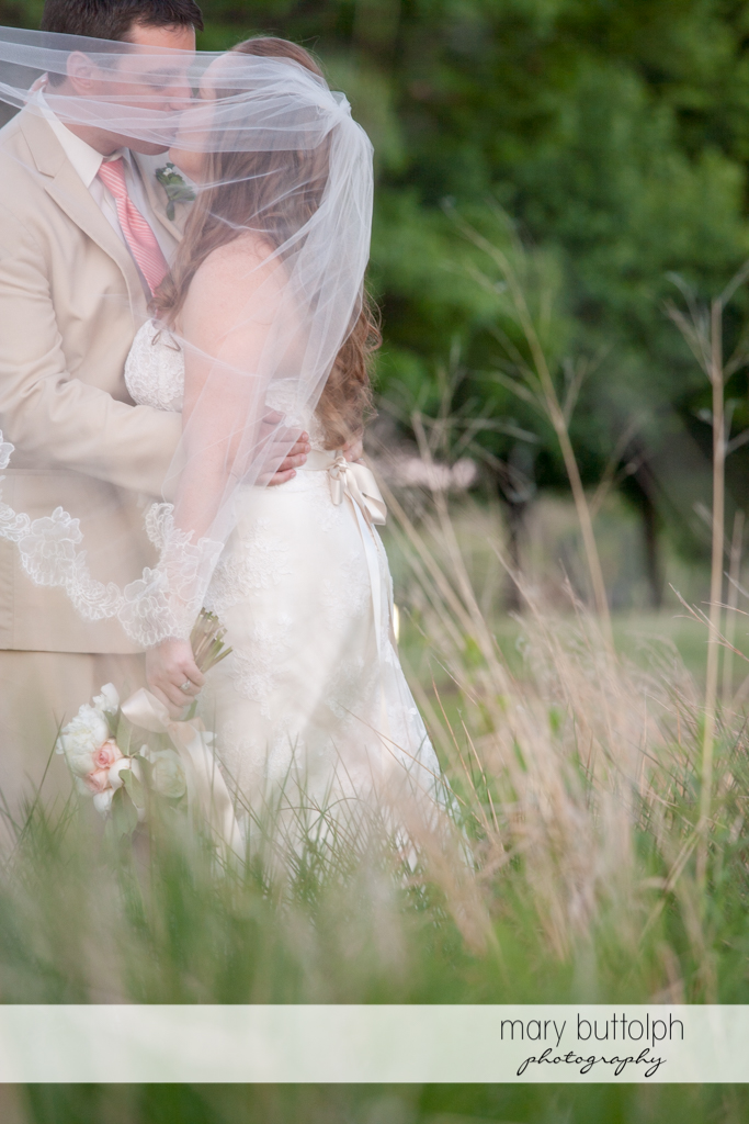 Veiled couple kiss in the garden at Emerson Park Pavilion Wedding
