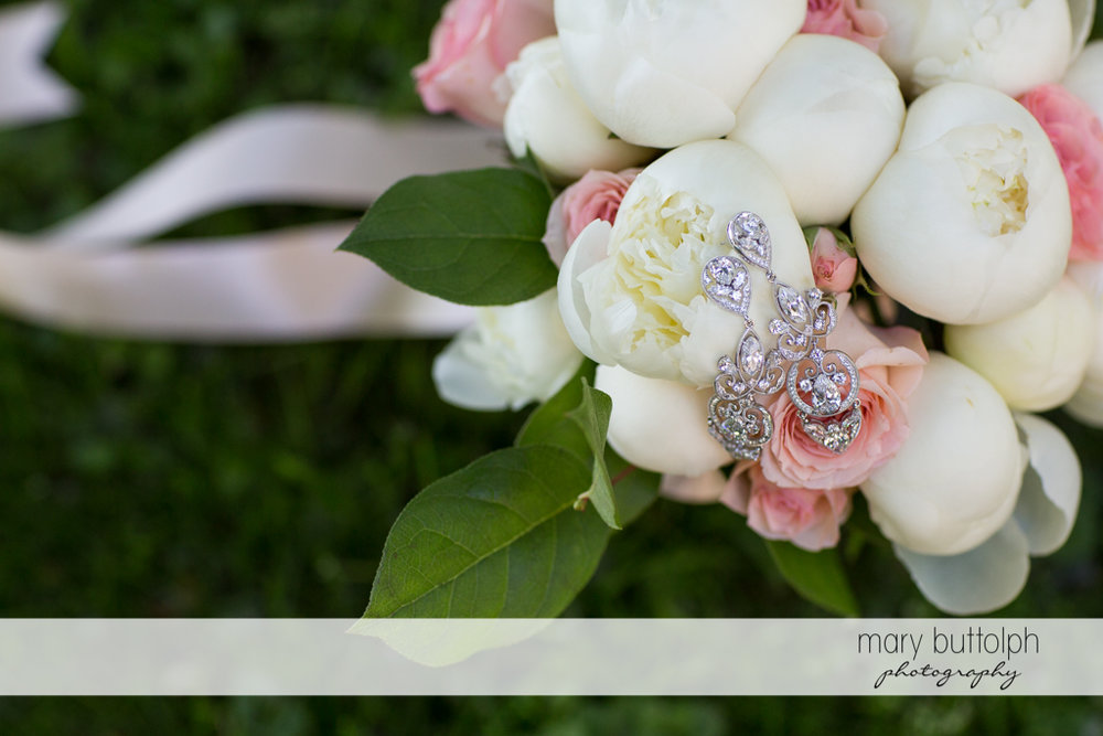 Close up shot of the bride's earrings on top of a bunch of flowers at Emerson Park Pavilion Wedding