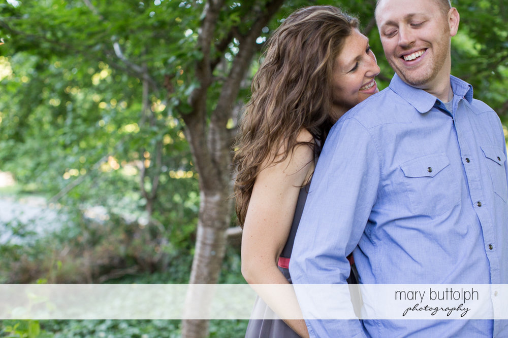 Couple smile near the trees in the garden at Franklin Square Engagement