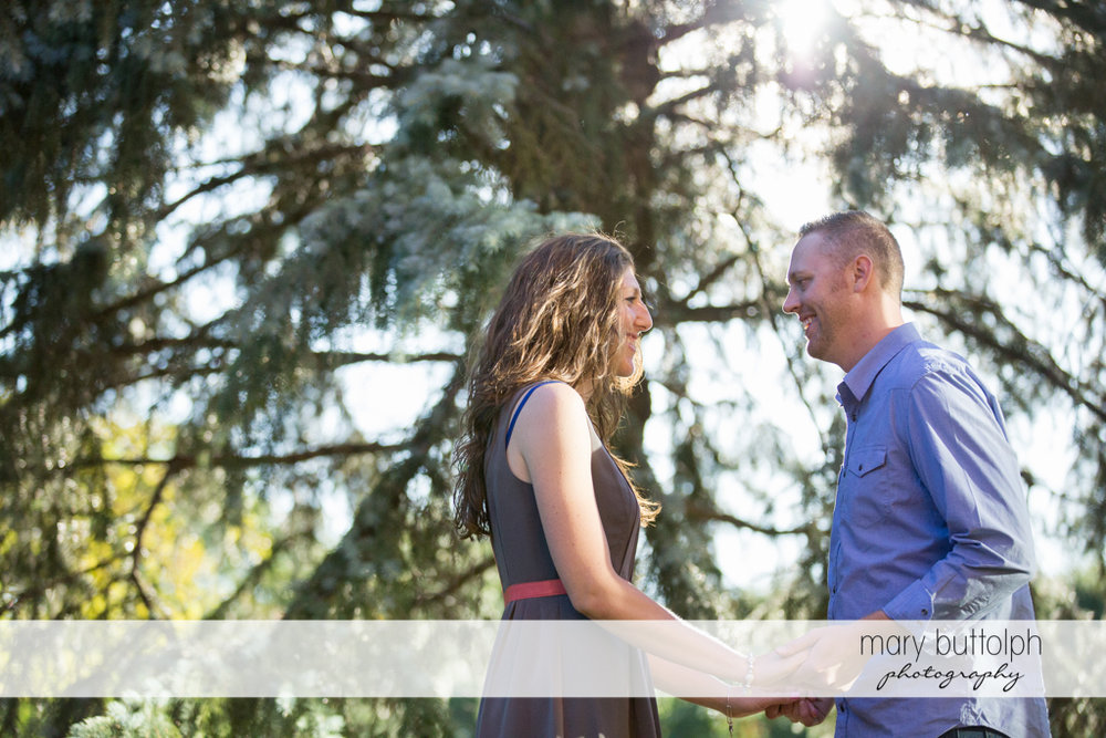 Couple face each other in the garden at Franklin Square Engagement