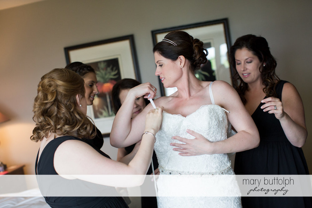 Bride slips into her wedding dress with the help of friends at the Inns of Aurora Wedding