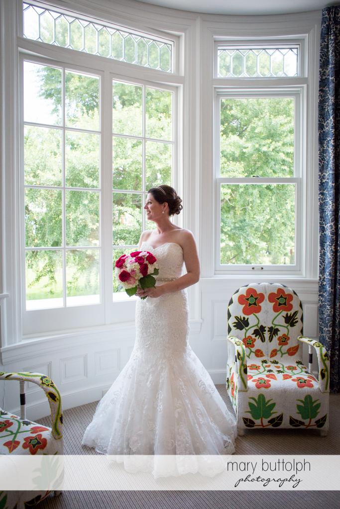 Bride admires the view outside at the Inns of Aurora Wedding