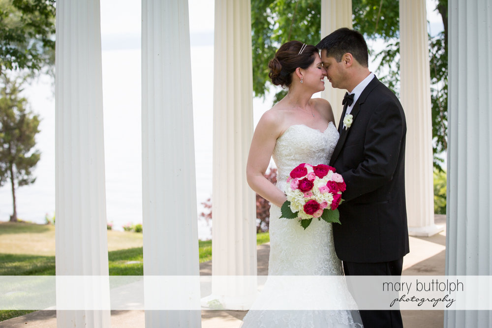 Couple rub noses under the gazebo at the Inns of Aurora Wedding