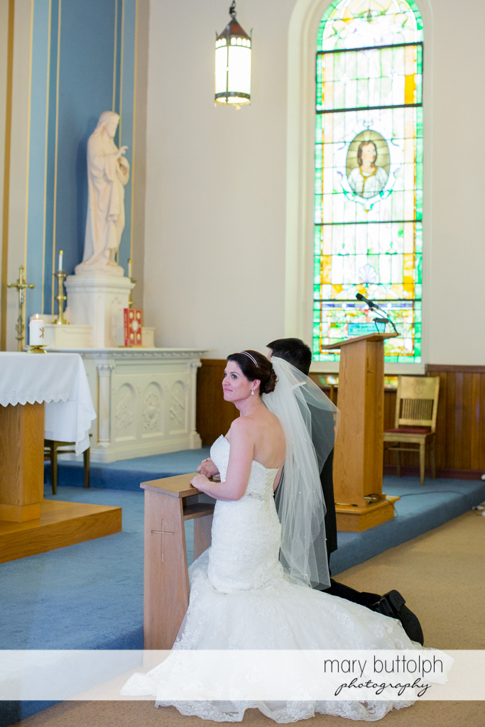 The couple kneel in front of the altar at the Inns of Aurora Wedding