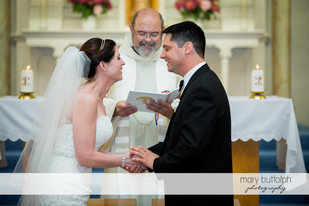 The couple face each other in front of the priest at the Inns of Aurora Wedding