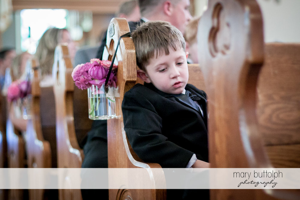 Young boy looks tired in church at the Inns of Aurora Wedding
