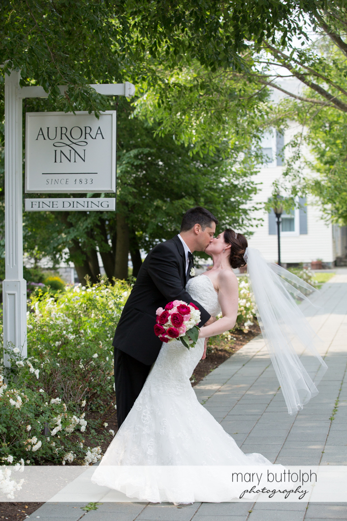 Couple kiss in front of the sign at the Inns of Aurora Wedding