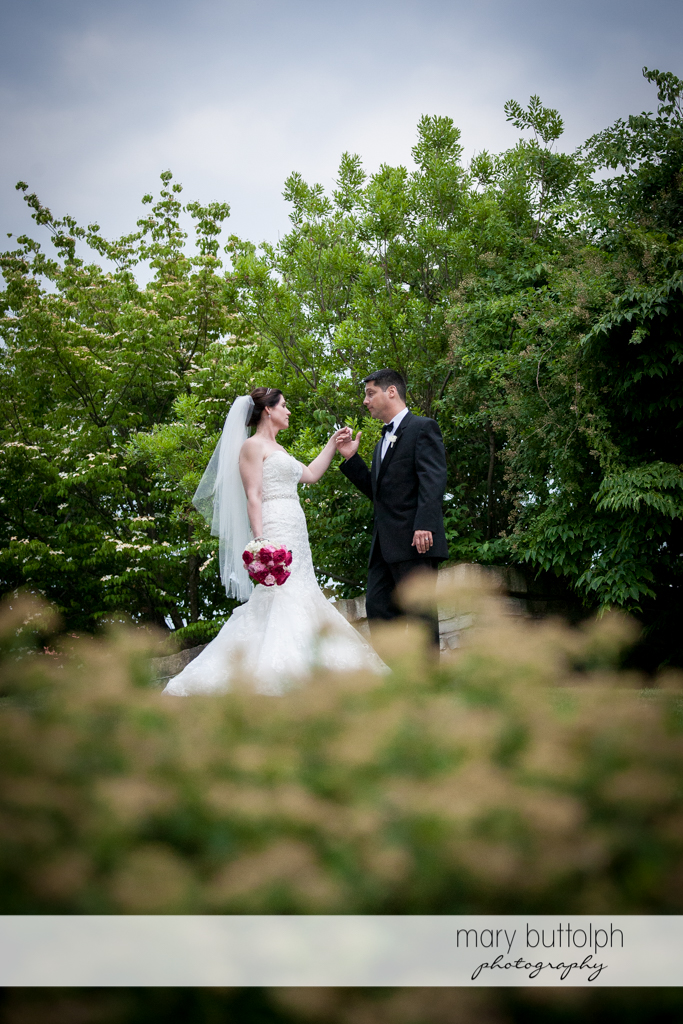 Couple hold hands in the garden at the Inns of Aurora Wedding