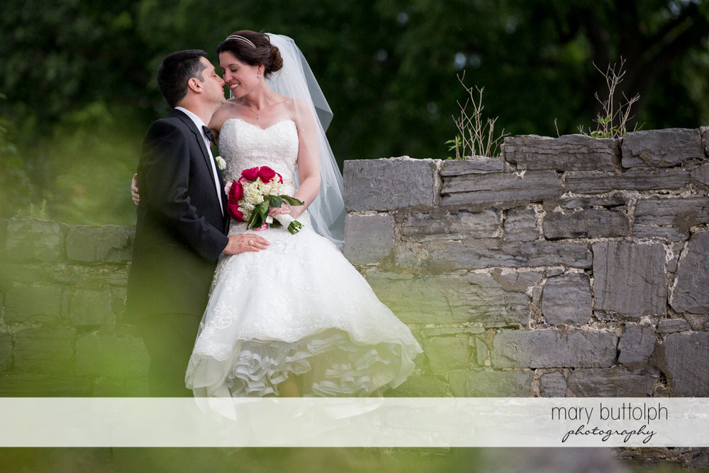 Couple rub noses in front of a stone wall at the Inns of Aurora Wedding