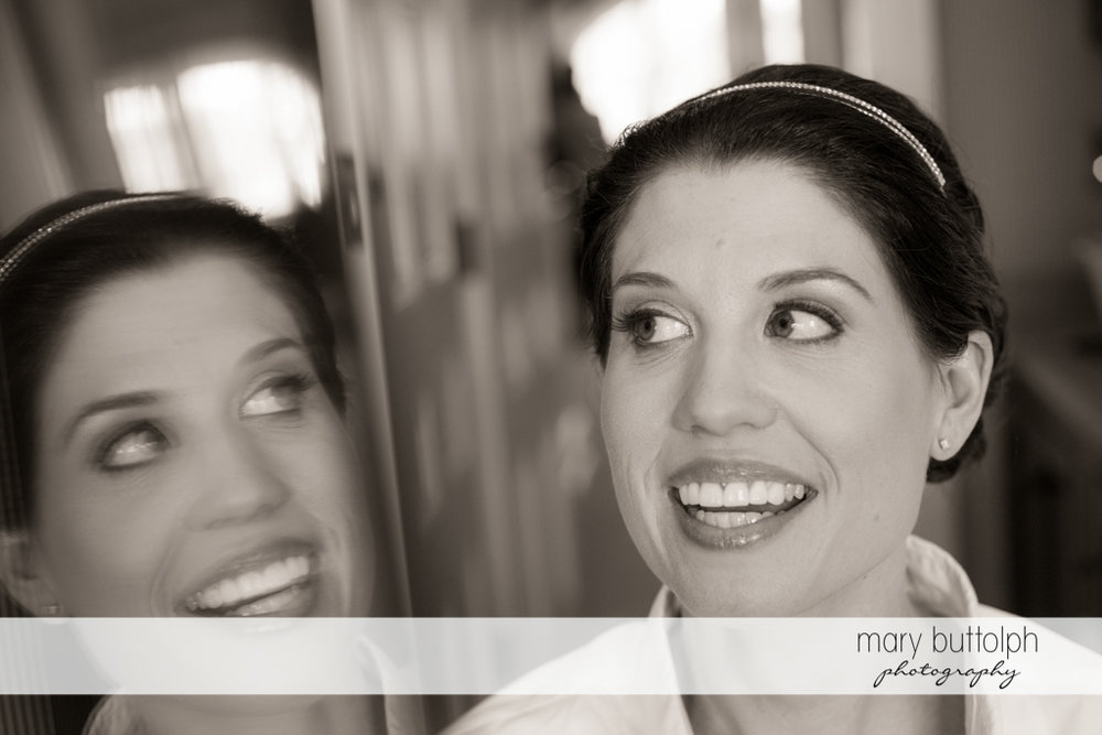 Bride's happy reflection in the mirror at the Inns of Aurora Wedding