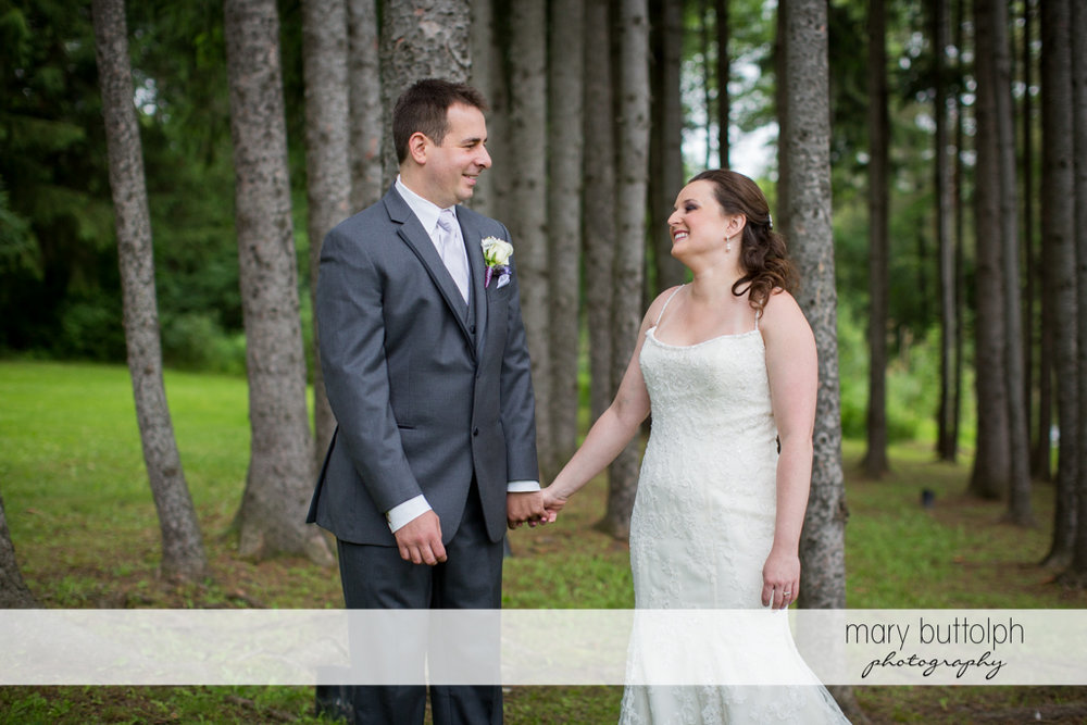 Couple hold hands in the woods at the Mirbeau Inn & Spa Wedding