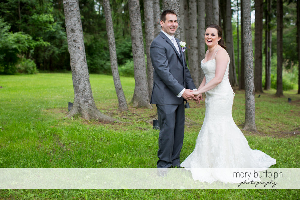 Couple face the camera in the woods at the Mirbeau Inn & Spa Wedding