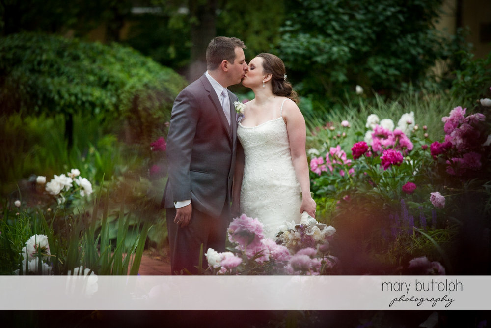 Couple kiss in the garden at the Mirbeau Inn & Spa Wedding