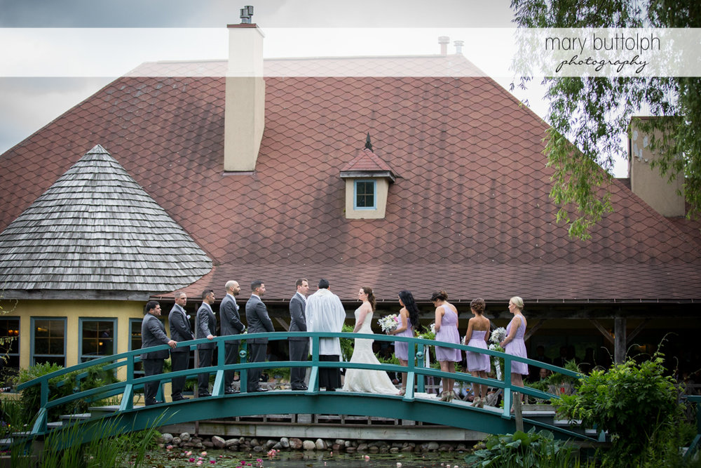 Back view of the wedding party and priest on the wooden bridge at the Mirbeau Inn & Spa Wedding