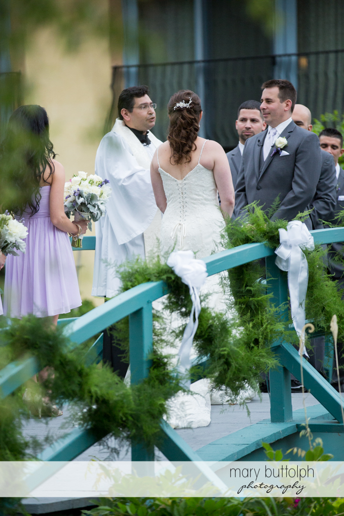 The priest talks to the couple on the bridge at the Mirbeau Inn & Spa Wedding
