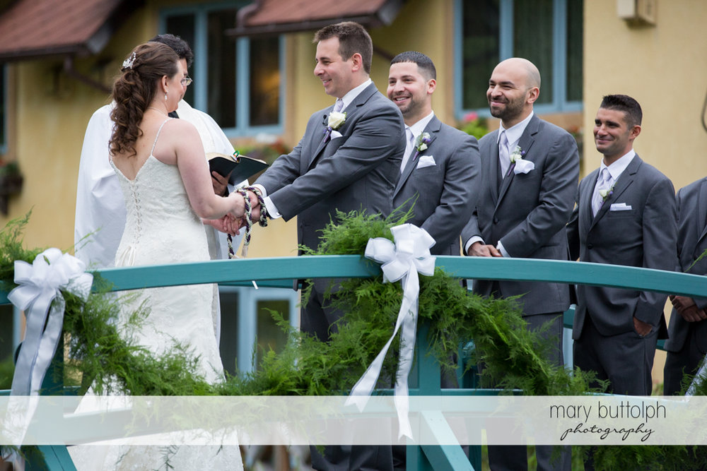 Couple hold hands during the wedding ceremony on the bridge at the Mirbeau Inn & Spa Wedding