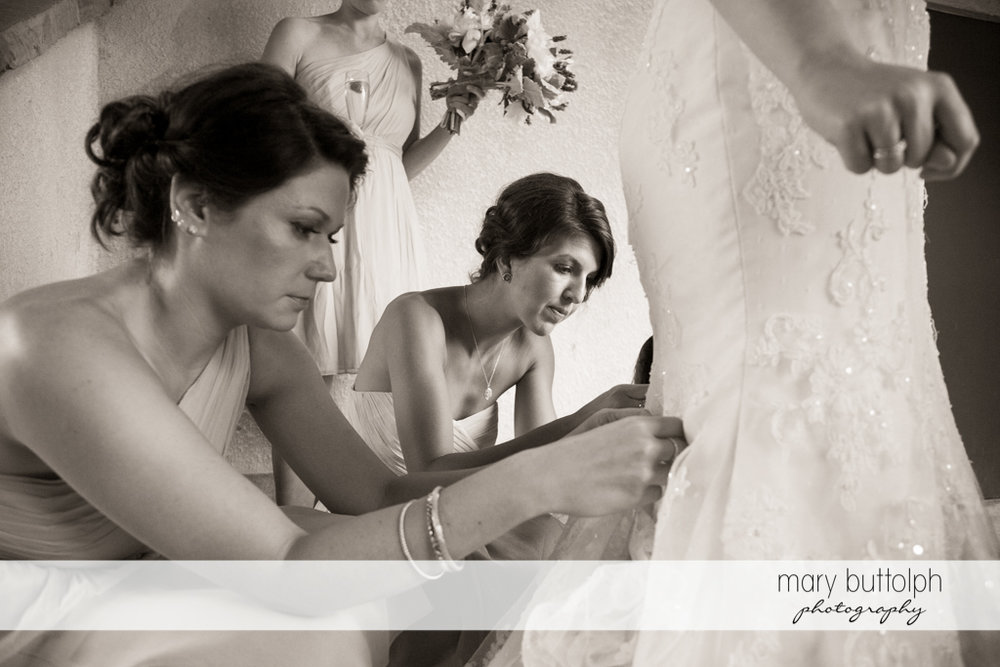 Bridesmaids busy fixing the bride's wedding dress at the Mirbeau Inn & Spa Wedding