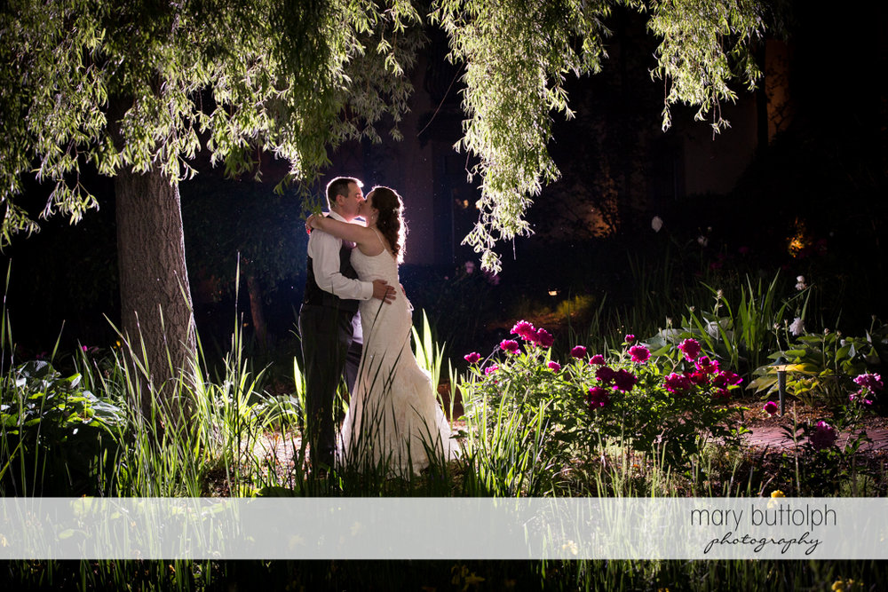 Couple kiss in the moonlight at the Mirbeau Inn & Spa Wedding