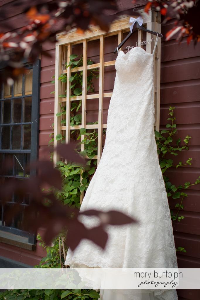 Bride's wedding dress hangs from a wooden trellis at the Sherwood Inn Wedding