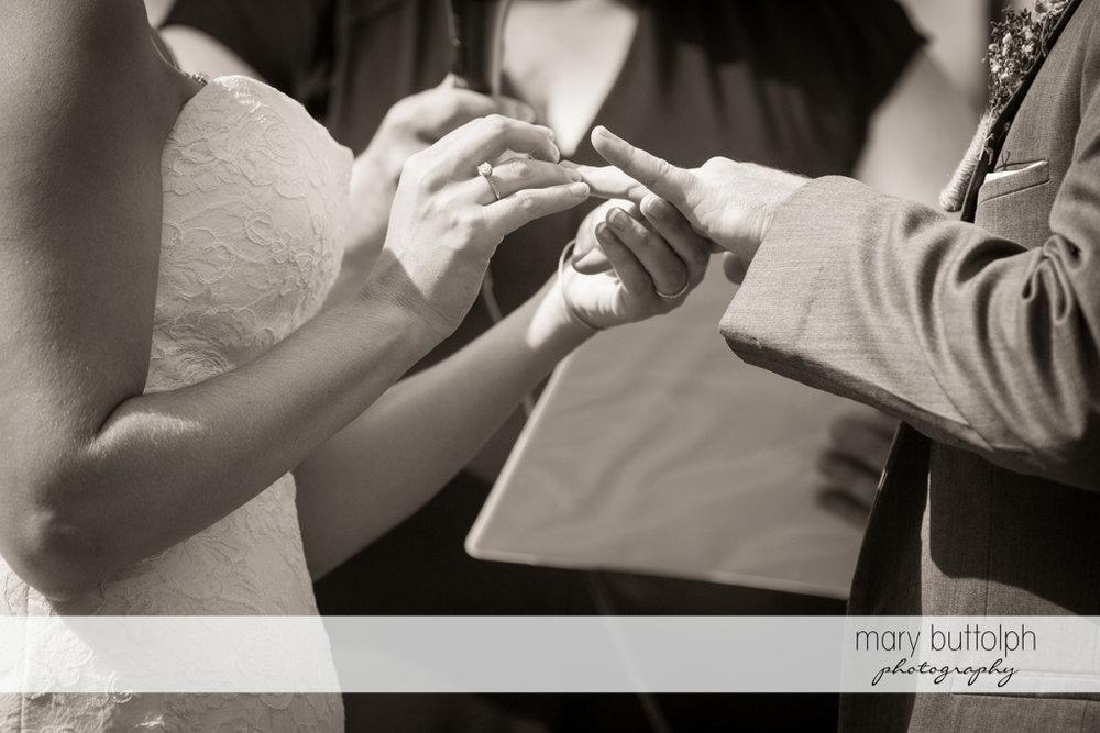 Bride slips the wedding ring on the groom's finger at the Sherwood Inn Wedding