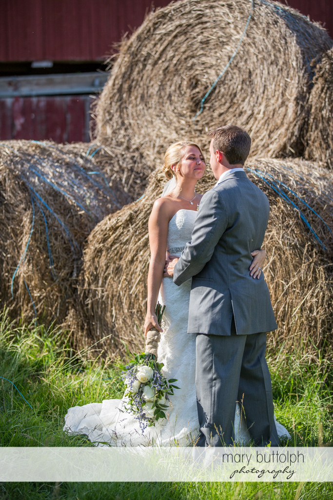Couple pose in front of haystacks at the Sherwood Inn Wedding