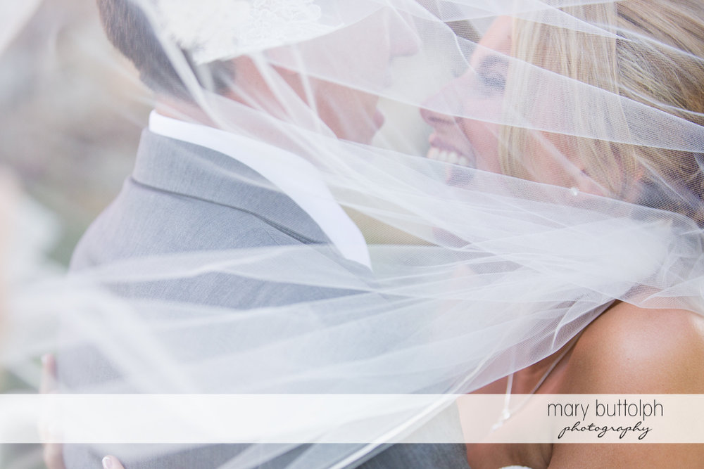 The couple's faces are covered by the bride's wedding veil at the Sherwood Inn Wedding